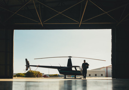 Pilot arriving at the airport with a helicopter in hangar