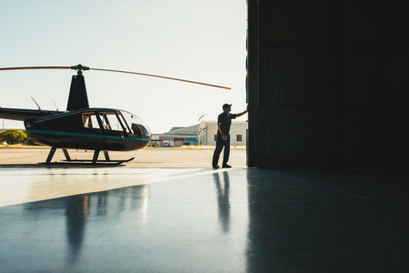 Mechanic opening the door of a airplane hangar
