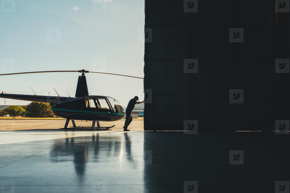 Pilot opening the helicopter hangar door