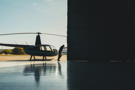 Pilot opening the helicopter hangar door