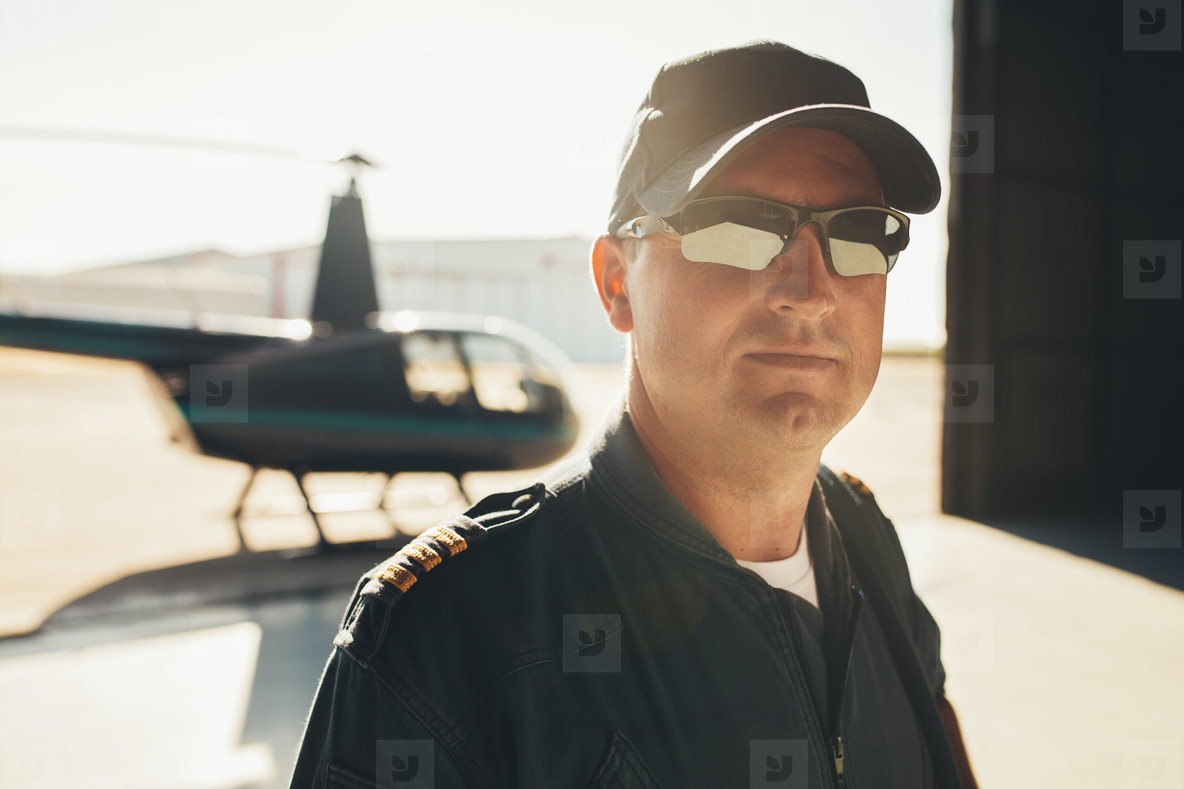 Professional pilot standing in airplane hangar