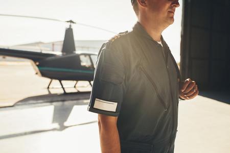 Professional pilot in uniform standing in airplane hangar