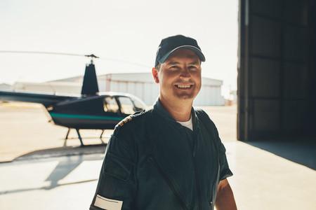 Happy male pilot standing in airplane hangar