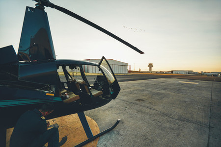 Pilot doing pre flight inspection at helicopter
