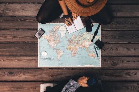 Couple planning vacation sitting by the world map