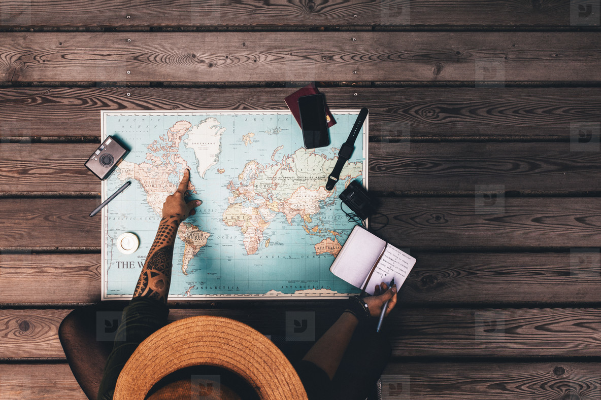 Woman planning vacation using a world map