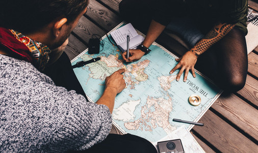 Couple making vacation plan sitting by the world map
