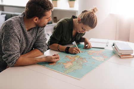 Young couple exploring the world map