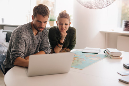 Young couple exploring the world on laptop computer