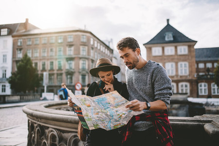 Young tourist couple exploring a city map