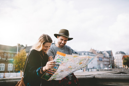Young tourist couple looking at a navigational map