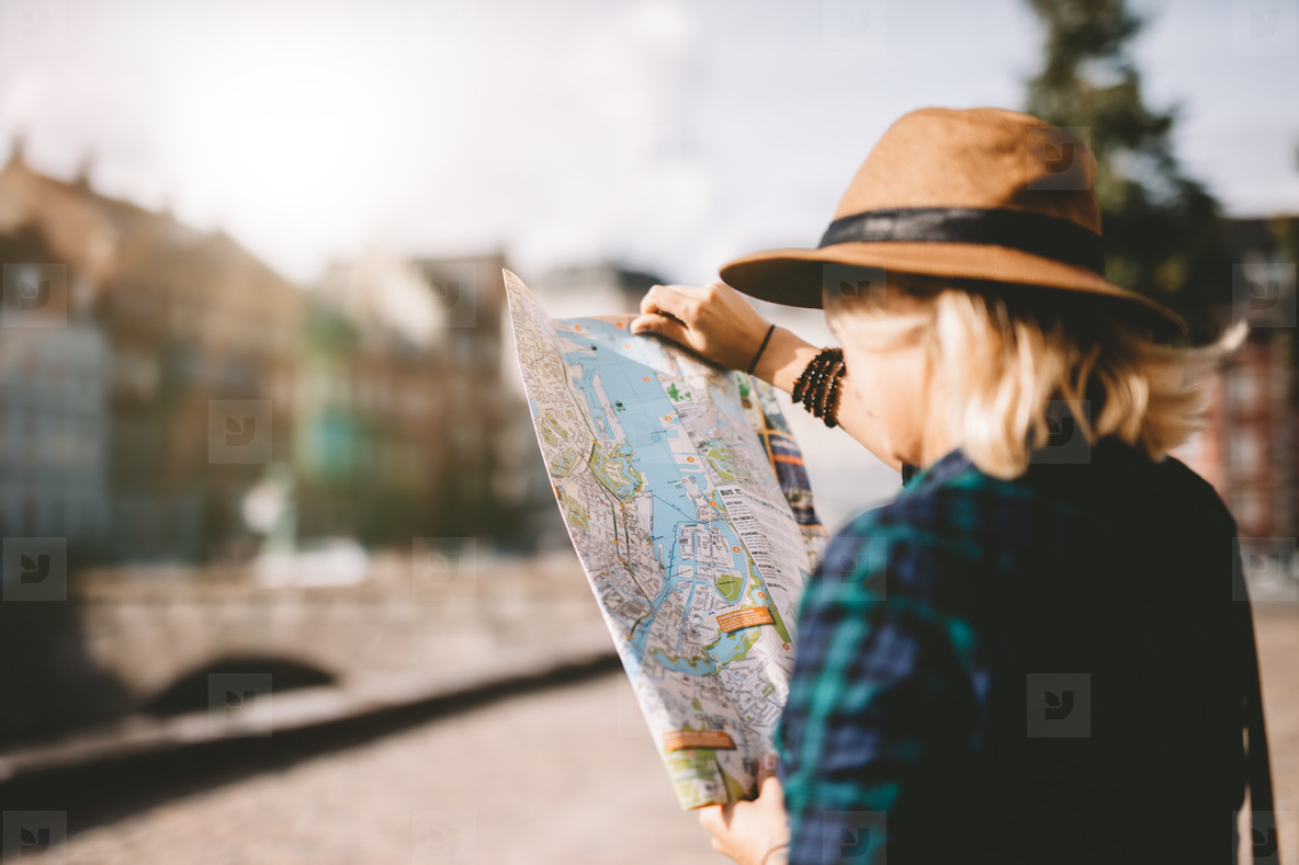 Young tourist woman searching right direction on map