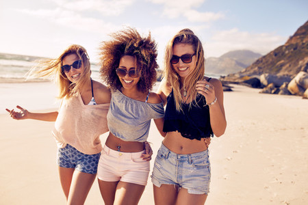 Young women strolling along a beach