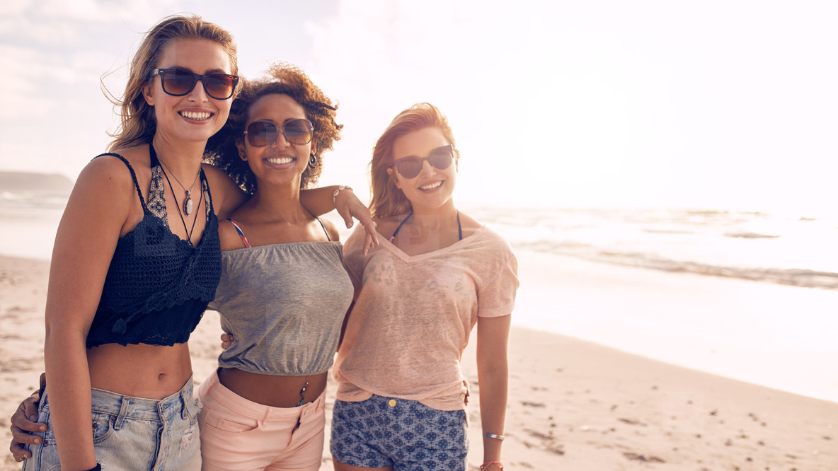 Three young female friends on the sea shore