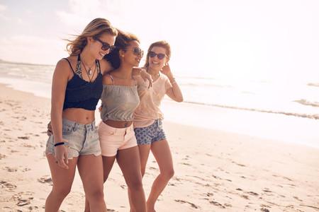 Young friends walking along a beach during summertime