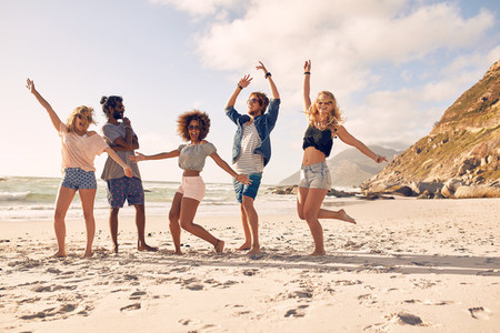 Happy young people dancing on the beach