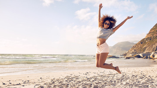 Beautiful young woman jumping at the beach