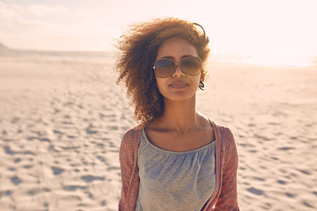 Attractive young woman standing on a beach