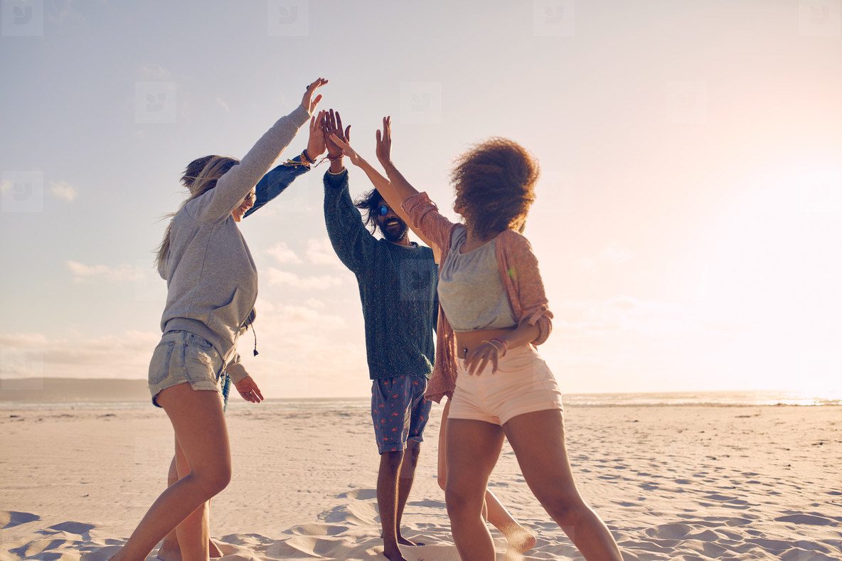 Group of happy friends high fiving on the beach