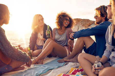 Group of smiling friends chilling on the beach