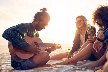 Young man playing guitar for friends on the beach