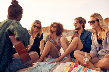 Group of people listening to friend playing guitar at the beach