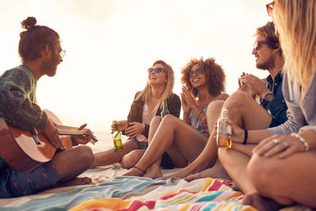 Group of smiling friends having fun at the beach
