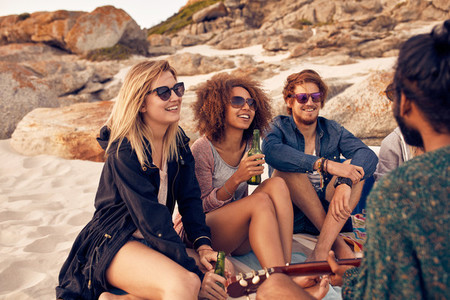 Friends enjoying a beach party with music and drinks