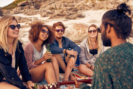 Diverse group of friends hanging out at beach