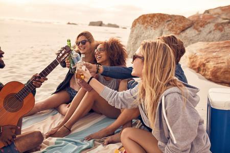 Multi ethnic friends enjoying beverages on the beach