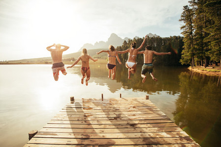 Young people jumping from pier into lake together