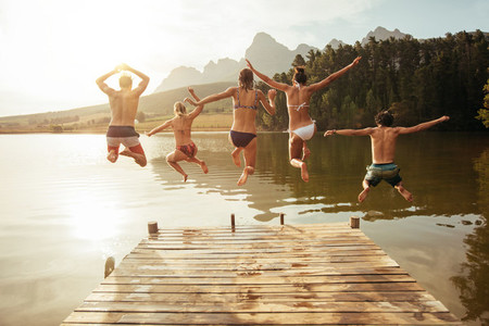Young friends jumping into lake from a jetty
