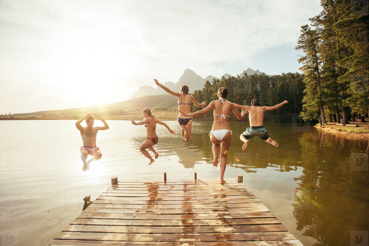 Friends jumping into the water from a jetty
