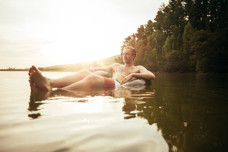 Young man in lake on inflatable ring