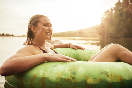 Happy young woman in lake on inflatable ring