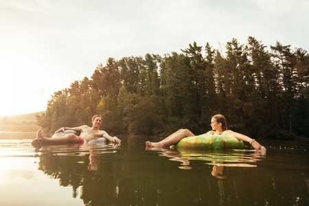 Young couple in lake on inflatable ring
