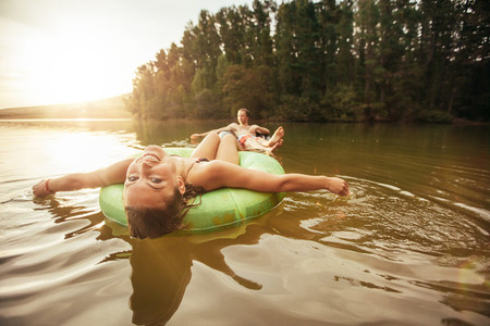 Young woman in lake on inflatable rings