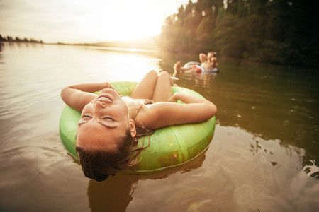 Young woman relaxing on inflatable ring in lake