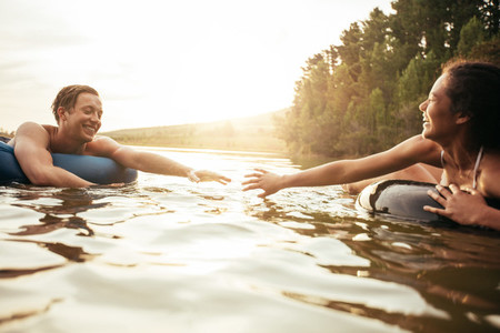 Affectionate young couple floating on inner tubes in lake