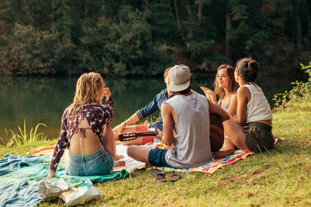 Young people having picnic near a lake