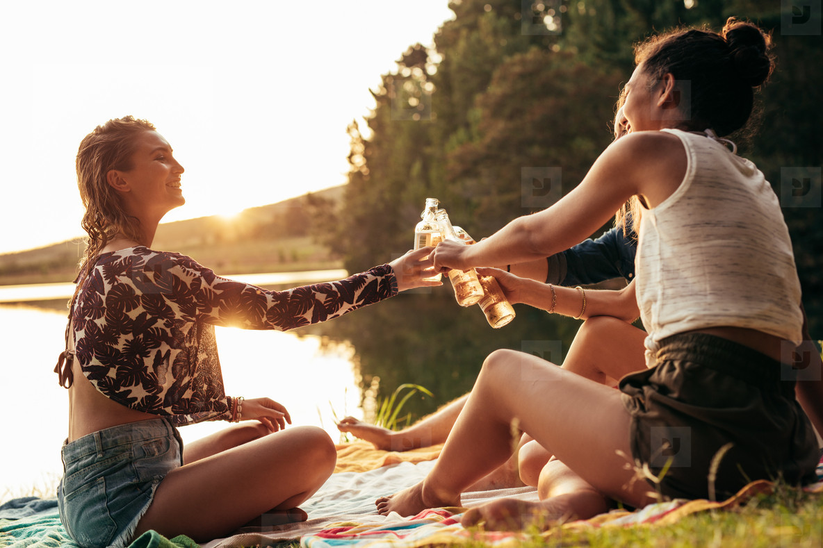 Young women celebrating at a lake