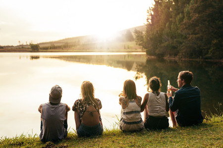 Young people sitting in a row by a lake
