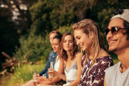 Happy young woman sitting with her friends by a lake