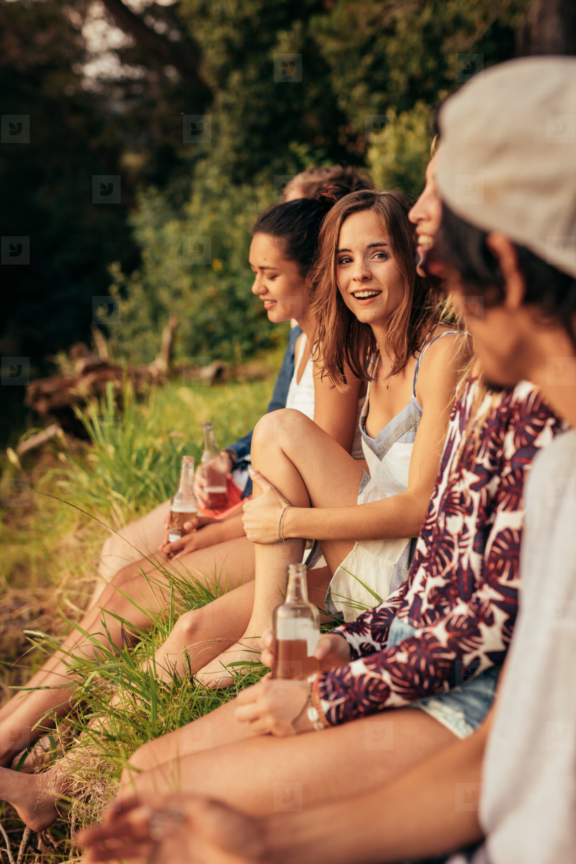 Young woman sitting with her friends by a lake