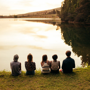 Group of young friends sitting in a row by a lake