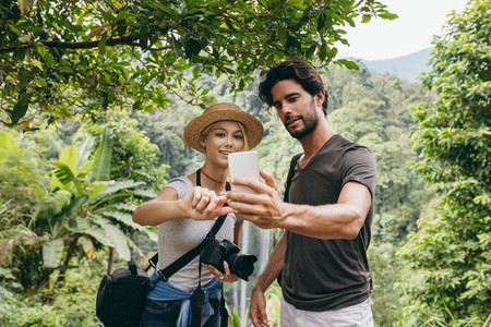 Couple taking a self portrait in forest