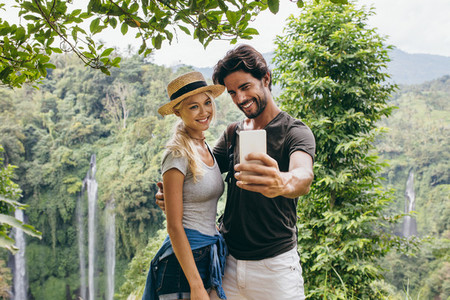 Couple taking selfie with waterfall in background