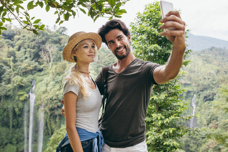 Loving couple taking selfie in forest