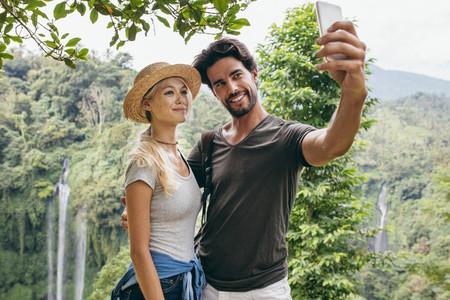 Loving couple taking selfie in forest