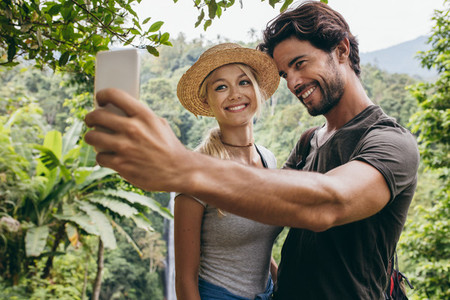 Smiling young couple taking selfie with waterfall